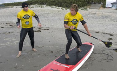 Simon Bassett teaches a student to SUP